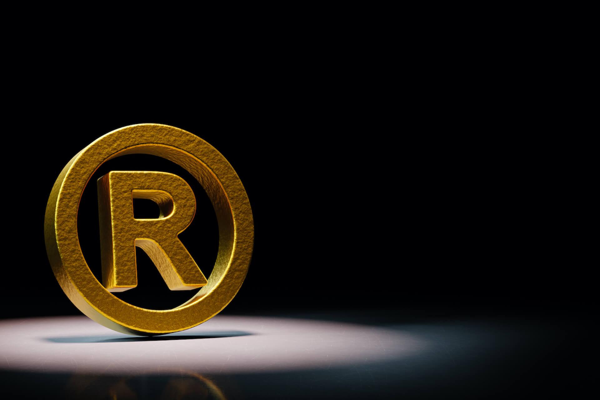 golden-trademark-symbol-spotlighted-black-background(2)