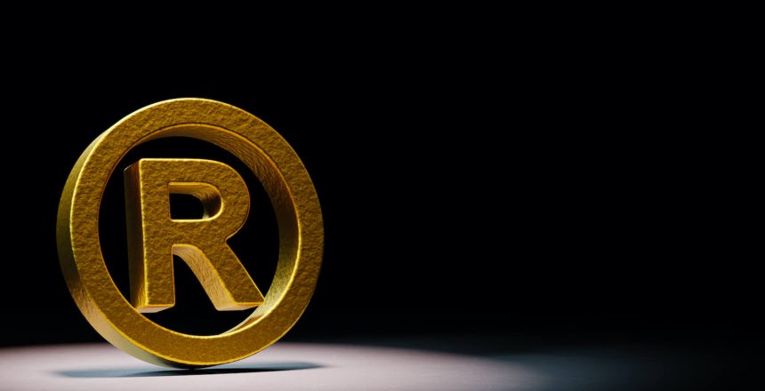 golden-trademark-symbol-spotlighted-black-background(2)